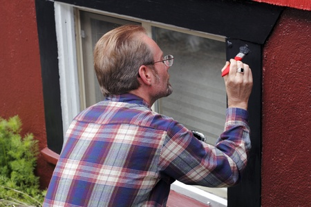 Man painting house window trim with black paint outdoors in the day. photo