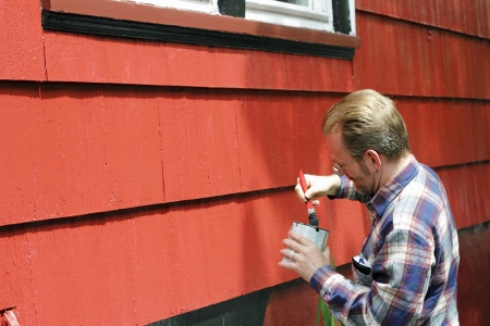 outside of house: Mature male dipping a paintbrush in a can of black paint in order to touch up trim around the windows of his house on a sunny day. Stock Photo