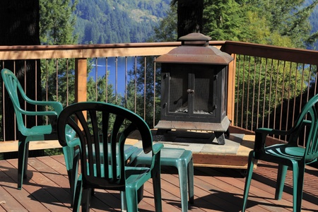 outdoor fireplace: Four plastic chairs on a scenic sunny outdoor deck with a fireplace on a raised platform and a small table all surrounded by a wood and metal railing. Stock Photo