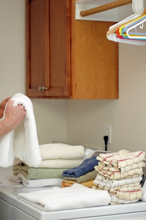 laundry room: Male hands folding a bath towel with other clean folded towels on top of a dryer in a home laundry room.