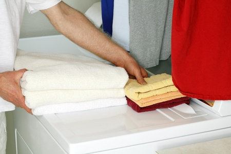 Adult male picking up folded towels from the top of a dryer in a laundry room to put them away.