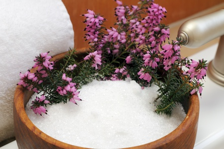 near side: Pink heather flowers in a wood bowl filled with Epsom salts on the top side of a white bath tub near a white cotton towel and silver faucet.