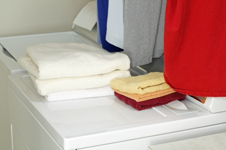 Piles of bath and hand towels folded on top of a dryer and washer along with five shirts hung up ready for storage.