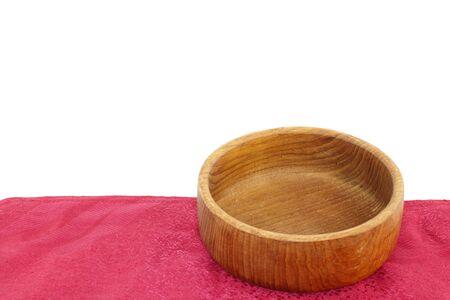 Cuenco vacío de madera de teca en un mantel de color rojo aisladas sobre un fondo blanco. Foto de archivo - 11186669