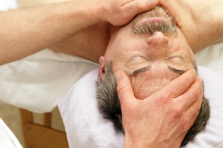 man with a goatee: Mature Caucasian man in his 50s relaxing on a massage table with his eyes closed receiving a face massage from a massage therapist.