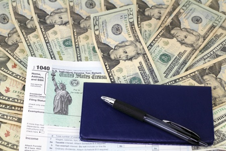 Pen and checkbook on top of tax refund check on a 1040 tax form on lots of paper cash ready to be deposited. Stock Photo