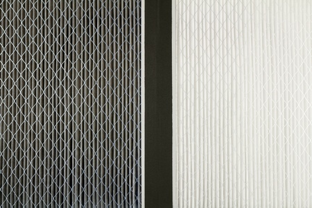 Close up side by side comparison of a dirty gray home air filter next to a clean white house furnace air filter.