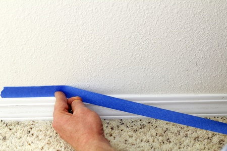masking tape: Male hand preparing to paint wall trim by placing blue painter Stock Photo