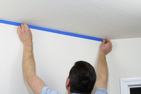 masking: Man preparing to paint ceiling by masking off the wall beneath it with blue painter