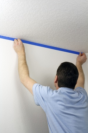 putting up: Adult male pressing blue painter Stock Photo