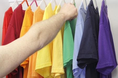 Male arm and hand picking out a green t-shirt from a mixed variety of shirt colors in the closet. Standard-Bild