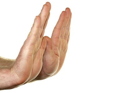 Adult male hands seen from the side with palms raised up in a stop gesture in front of a white background.