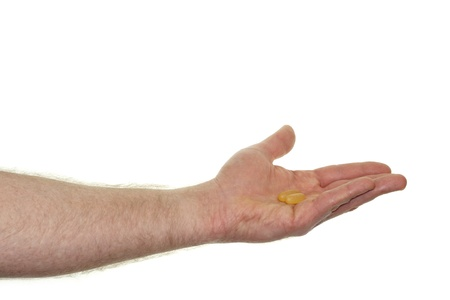 Caucasian hand showing a dose of a fish oil soft gel supplement in front of a white background.  photo