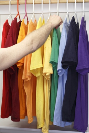 Arm and hand of a caucasian man seen choosing a t-shirt from a variety of shirts in a rainbow of colors in a closet. photo