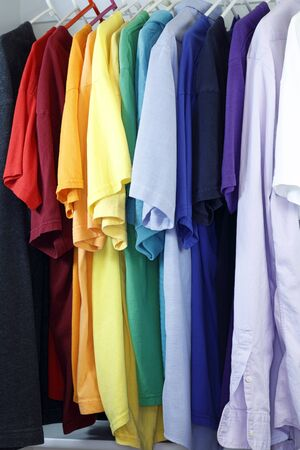 menswear: Colorful assortment of menswear shirts hanging from a clothes rack in a closet.
