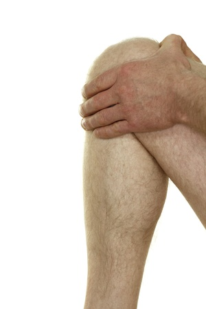 Nude middle aged knee of a man in his forties raised up being held by his hands because he is suffering from knee pain in front of a white background. photo