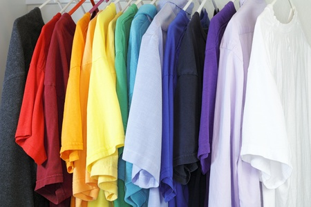 Variety of shirts for a man to wear in a many different colors and styles hanging in a closet. Foto de archivo