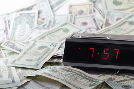drowse: Older digital clock with a drowse button ticking time with United States paper dollars of various amounts all around randomly. Stock Photo