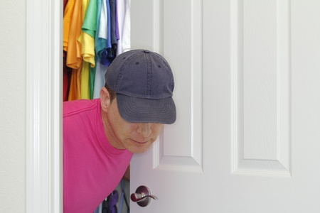 Man dressed in a pink shirt and blue hat comes out of the closet that has a rainbow of colorful clothes hanging in it. photo