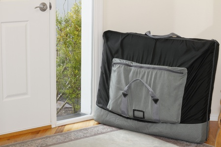 Outcall massage table in a black nylon carrying case leaning against an interior home foyer wall.