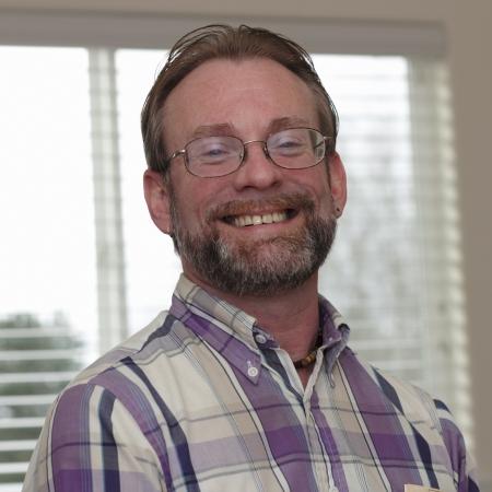 Male wearing eyeglasses in is forties with blonde gray hair and beard smiling in a joyous way showing his upper teeth  Standard-Bild