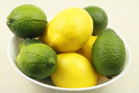Five limes and four lemons in a white bowl on a tan counter  Standard-Bild