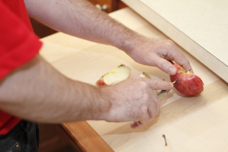 paring knife: Hands of a man cutting a red apple on a wood cutting board with a kitchen paring knife.