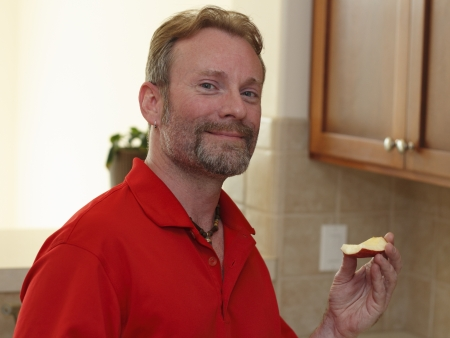 Mature man with a beard and slight smile looking at viewer while holding up an apple wedge in a kitchen.