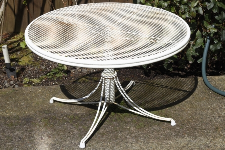 small table: Small round metal patio table painted white aged with dirt and rust needing a good painting. Stock Photo