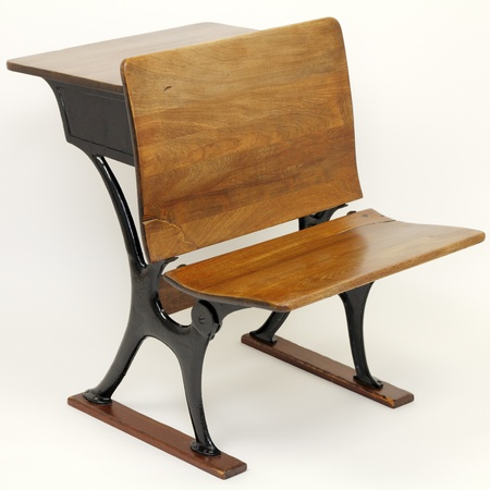 One vintage metal and wood school desk and school chair combination with a desk in back and a chair in the front.  photo