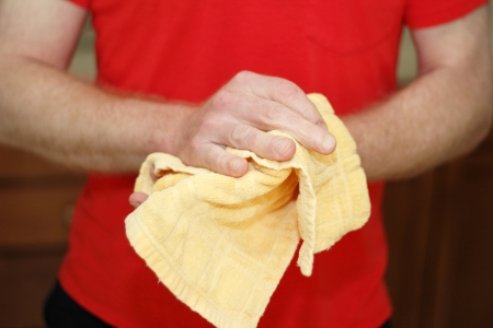 Adult male caucasian wearing a red shirt drying hands on a yellow cotton cloth dish towel close up.