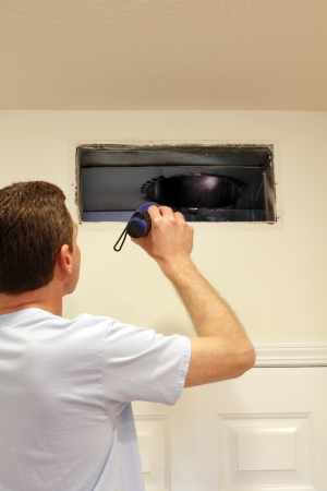 air: Adult male shining a flashlight into an air duct return vent to check for any need of cleaning dust or any other maintenance.