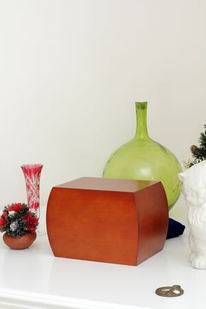 cremated: Wood urn filled with loved ones ashes surrounded by memento objects on a white mantle.