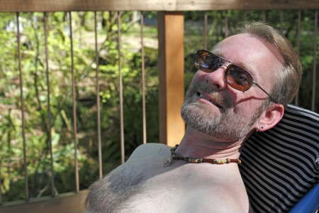 without: Relaxing adult caucasian male without a shirt on is seen close up leaning back in a chair on an outdoor patio deck and smiling at the viewer on a spring day.