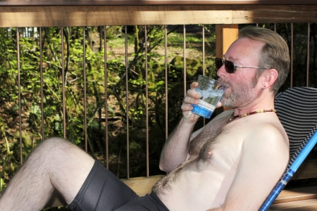Man in his forties without a shirt on leaning back in a patio lounge chair drinking a glass of ice water from a clear glass outside on a spring day. photo