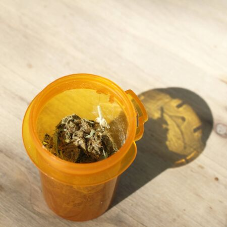 Medical marijuana in an orange brown prescription bottle with its top off so you can see the marijuana inside outside on a sunny day. photo
