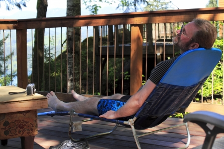 Man relaxing on a lounge chair on an outdoor deck in a forest with his eyes closed.