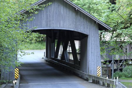 crist: West side of very old gray wood covered paved two lane bridge over Cedar Creek near Crist Mill surrounded by tree foliage.  Stock Photo