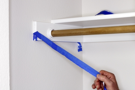 Blue painter s tape being pulled off of closet shelf bracket after painting the closet walls white   Stock Photo