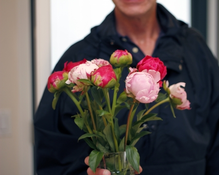 Dressed in a black coat with a bright open door behind him a man offers the viewer a glass vase filled with pink and red peony flowers   photo