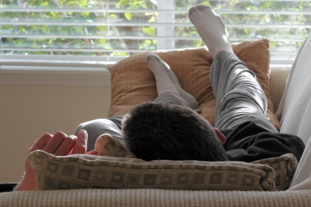 Adult caucasian male laying with his head on a pillow on a couch