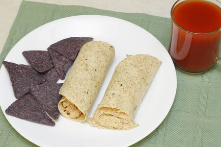 corn tortilla: Salmon salad tortilla rolls with blue corn chips on the side as well as a glass of vegetable tomato juice   Stock Photo