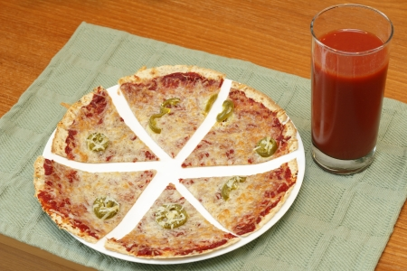 glass topped: Sliced thin crust tortilla pizza topped with tomato paste, mozzarella cheese, jalapenos and pepper along with a tall glass of tomato vegetable juice