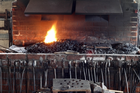 coals: Historic brick blacksmith stove with blacksmith tools in front and a fire burning from coals on top under vents
