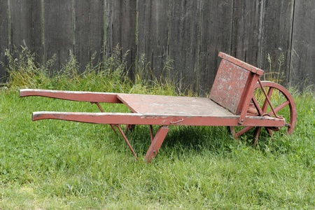 barrow: Very old wheel barrow made of wood and metal, painted red, sitting in a grassy field in front of an old wood fence