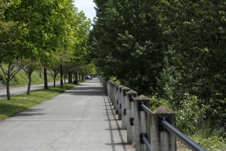 VANCOUVER, WASHINGTON - MAY 25: Long public sidewalk that is popular for walking and biking that travels along natural areas with trees by the Columbia river on May 25, 2012 in Vancouver, Washington.
