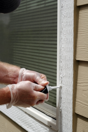 Vinyl gloved hands with tube of white caulking filling holes that developed in a home outdoor window frame