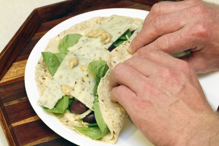 Hands wrapping flavored cheese, spinach, kalamata olives and mustard in a soft multi grain tortilla for lunch