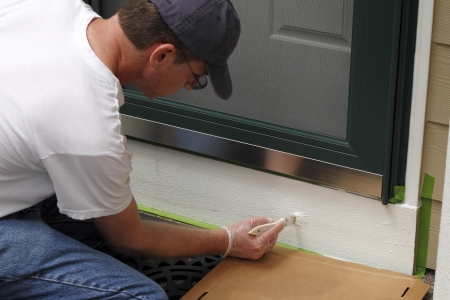 Adult male painting the white part below the front door of his home to make the entry way more inviting and better looking