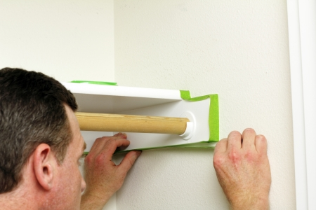 prep: A man is preparing to paint the closet walls by putting on green painter